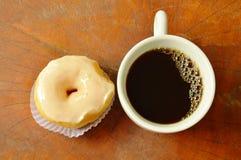 butées toriques crèmes blanches et tasse de café noir sur le conseil en bois photo libre de droits