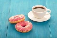 Butées toriques roses avec une tasse de café sur une table en bois Image libre de droits