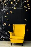 Butaca amarilla brillante enfrente de una pared negra imagen de archivo
