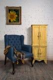 Butaca azul del vintage, armario amarillo y pintura enmarcada Foto de archivo