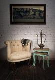 Butaca beige vieja, tetera de cobre amarillo, pintura colgada y tablas jerarquizadas foto de archivo