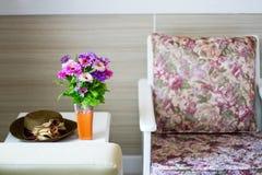 Butaca cómoda con las almohadas y la manta contra la pared blanca Imagenes de archivo