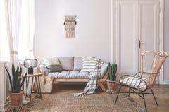 Butaca cerca del sofá beige con las almohadas en interior de la sala de estar con las plantas y la puerta Foto verdadera fotografía de archivo