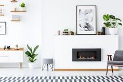 Butaca gris al lado de la chimenea debajo del cartel en inte de la sala de estar imagenes de archivo