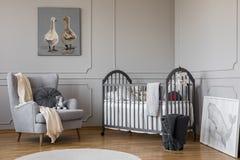 Butaca gris cómoda con la almohada redonda y la manta blanca al lado del pesebre de madera con las almohadas y los juguetes, espa fotografía de archivo