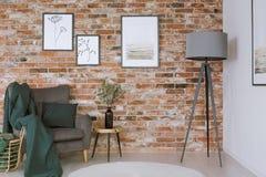 Butaca gris contra la pared de ladrillo foto de archivo libre de regalías