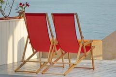 Butaca plegable de madera dos en el patio de la playa de la opinión del mar imagen de archivo