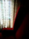 Butaca roja con las cortinas elaboradas detrás Imagen de archivo libre de regalías