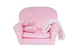 Butaca rosada con las almohadillas, manta de Comfi en ella Imagen de archivo libre de regalías