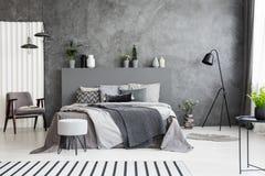 Butaca y taburete grises cerca de la cama con el cabecero en el dormitorio inter Imágenes de archivo libres de regalías
