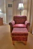 Butaca y taburete rojos elegantes en la alfombra Fotos de archivo
