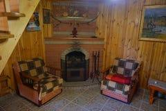 Butacas por la chimenea El interior de una de las pensiones de Ucrania occidental fotografía de archivo
