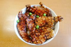 Butadon för bästa sikt bunke av ris som överträffas med skivat griskött och träbakgrund för söt sauceon Royaltyfri Bild