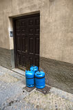 Butane gas cylinders at a house door. Three blue gas canisters on the pavement close to a house door Royalty Free Stock Photo