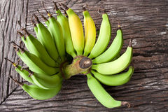 Butch of small  bananas on old wood table Stock Photography