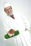 Butcher. Senior butcher holding a raw roastbeef on a tray Royalty Free Stock Photography