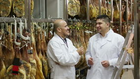 Butcher and assistant with jamon joints stock footage