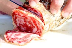 Butcher cut the salami with a very sharp knife 3 Royalty Free Stock Photos