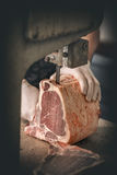 Butcher is cutting beef meat. With big electric saw at the meat manufacturing Royalty Free Stock Image