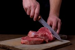 Butcher cutting beef meat on kitchen. Black text area Stock Images