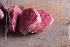 Butcher cutting beef meat on kitchen. Top view.  Royalty Free Stock Photo