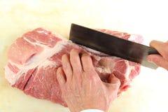 Butcher cutting a big piece of meat. A Butcher cutting a big pice of meat Royalty Free Stock Images
