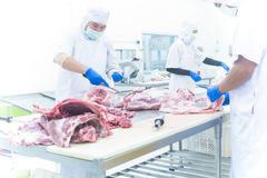 Butcher cutting the fresh meat in ham factory Stock Images