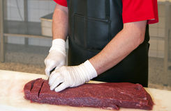 Butcher cutting meat Royalty Free Stock Image