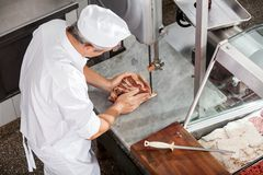 Butcher Cutting Meat With Bandsaw. High angle view of butcher cutting meat with bandsaw in butchery royalty free stock photos