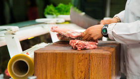 Butcher Cutting Meat with Cleaver. Butcher chopping meat on a wood block with cleaver showing motion blur royalty free stock photo