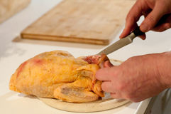 Butcher is cutting meat into pieces with knife Royalty Free Stock Image