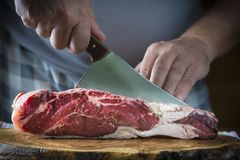Butcher cutting a piece of meat with a cleaver Stock Photography