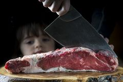 Butcher cutting a piece of meat with a cleaver while a baby girl Royalty Free Stock Image
