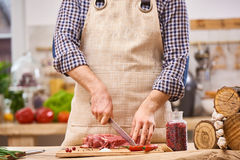 Butcher cutting pork, beef or mutton steak meat on kitchen with vegetables background Royalty Free Stock Photos