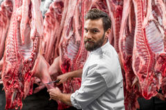 Butcher cutting pork at the manufacturing Royalty Free Stock Images