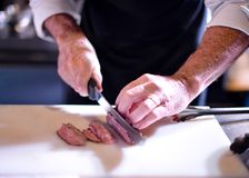 Butcher cutting pork meat, Chef cutting fresh raw meat, Chef cooking food in the kitchen royalty free stock image