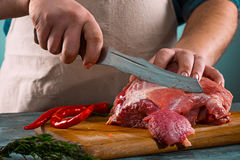 Butcher cutting pork meat on kitchen Stock Photography