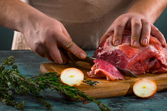 Butcher cutting pork meat on kitchen Stock Image