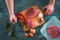 Butcher cutting pork meat on kitchen Stock Photo