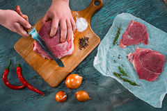 Butcher cutting pork meat on kitchen Stock Photos