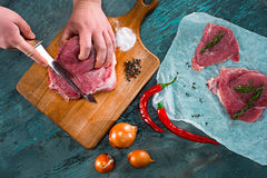 Butcher cutting pork meat on kitchen Royalty Free Stock Photos