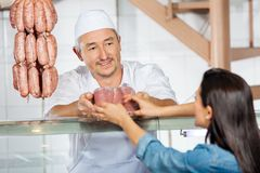 Butcher Giving Pack Of Sausages To Customer Stock Photography