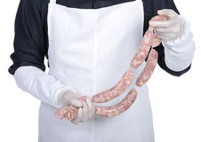 Butcher. Happy cook holding sausage and smiling. young butcher demonstrating work in hands Royalty Free Stock Photos