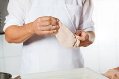 Butcher Holding Chicken Meat Covered With Flour Royalty Free Stock Images