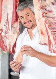 Butcher Holding Chicken Meat In Shop Stock Photo