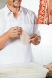 Butcher Holding Meat Covered With Flour Royalty Free Stock Images