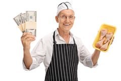 Butcher holding money stacks and chicken drums. Elderly butcher holding stacks of money and chicken drums isolated on white background Stock Images
