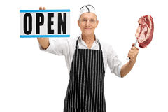 Butcher holding open sign and fork with steak Stock Photography