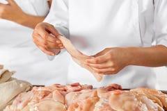 Butcher Holding Raw Chicken Piece In Butchery Stock Photos