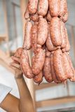 Butcher Holding Sausages In Butchery Royalty Free Stock Photos